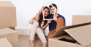Portrait of young couple looking through house-frame at new home