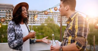 Two young casual friends having a casual conversation at an urban celebration with a cityscape view in the evening